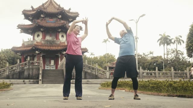 two active asian seniors stretching in local city park (slow motion) - pampering self stock videos and b-roll footage