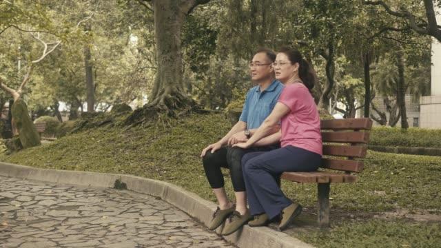 休憩を取り、公園に座っている2人のアクティブな先輩 - ベンチ点の映像素材/bロール