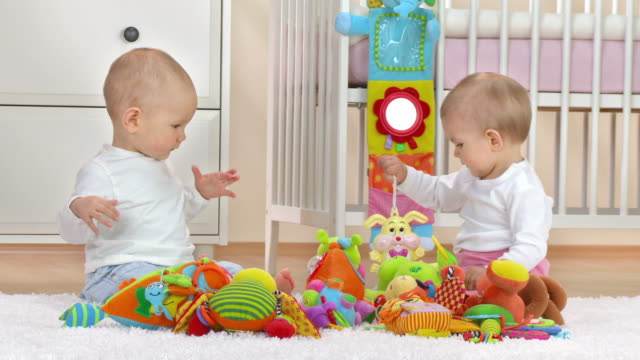 HD: Two Adorable Babies Playing With Toys