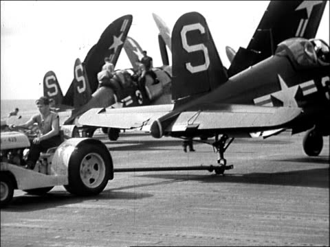 two adult caucasian male united states navy crewmen carrying airtoground rocket across flight deck adult caucasian male crewman driving a tractorlike... - 船の一部点の映像素材/bロール