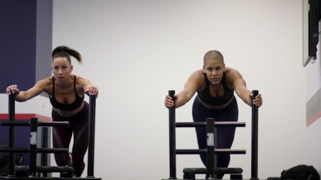 stockvideo's en b-roll-footage met twee volwassen vrouwtjes concurreren tegen elkaar binnen een sportschool duwen een gewicht-slee - fatcamera