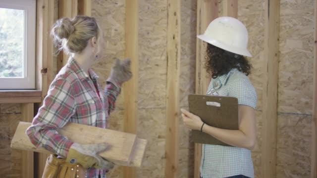 vidéos et rushes de deux femelles adultes discutant projet bâtiment bricolage maison - âges mélangés