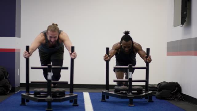 stockvideo's en b-roll-footage met twee volwassen mannen concurreren tegen elkaar binnen een sportschool duwen een gewicht-slee - fatcamera