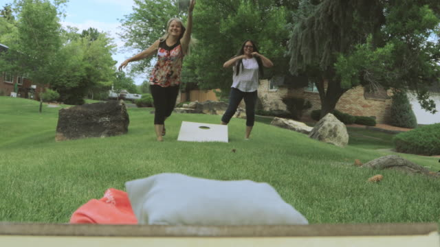 two adult senior female friends having fun together outdoors bean bag toss 4k video - game show stock videos & royalty-free footage