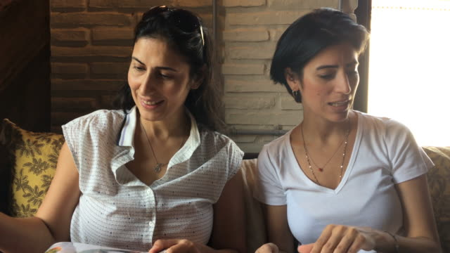 two adult women in the restaurant. looking to menu. - middle eastern ethnicity stock videos and b-roll footage