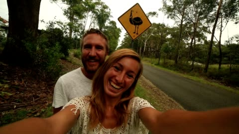 two adults take selfie portrait standing near emu warning sign - road warning sign stock videos & royalty-free footage