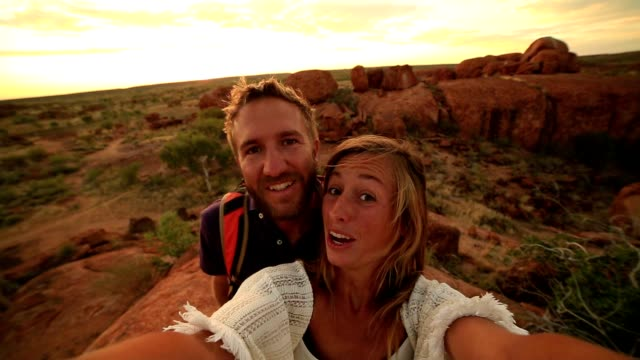 two adults take selfie portrait with spectacular landscape at sunrise - australian aboriginal culture stock videos and b-roll footage