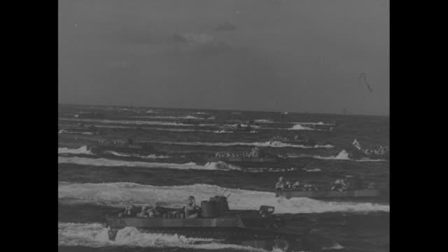 two aerial shots of assault boats carrying us marines heading towards shore / vs assault boats heading towards shore, interspersed with aerial shots... - battaglia di iwo jima video stock e b–roll