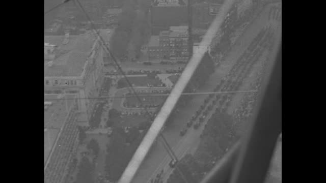 Two aerial shots through wing struts of camera plane of WWI victory parade down Pennsylvania Avenue in Washington DC flyover Victory Arch / Note...