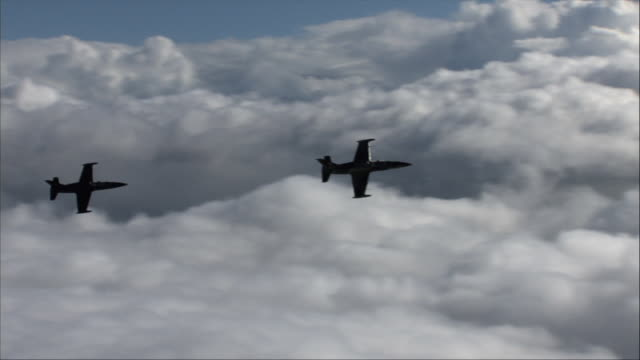 air to air, two aero l-39 albatroses flying above clouds and coastline - air to air shot stock videos and b-roll footage