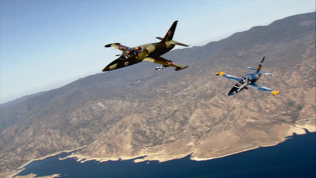 AIR TO AIR, MS, Two Aero L-39 Albatroses flying over Mojave Desert mountains and lake, California, USA