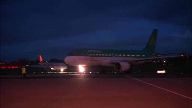 two aeroplanes move on airport runway, belfast international airport, northern ireland - グランドキーパー点の映像素材/bロール