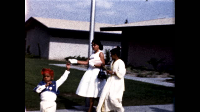 two african american boys in identical clothing with red hats standing next to a pole two women in white dresses walk across the lawn - matching outfits stock videos & royalty-free footage
