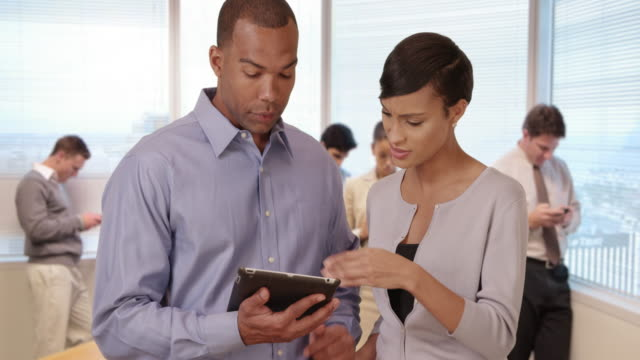 Two African American business professionals discuss work on their tablet