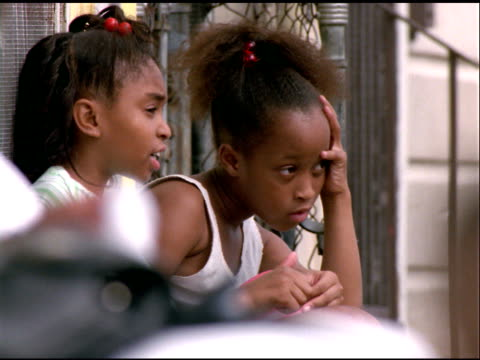two african american girls sit on steps looking bored - postura video stock e b–roll