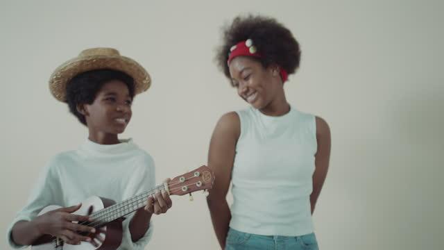 vídeos de stock, filmes e b-roll de duas crianças africanas gostam de tocar música. - ukulele