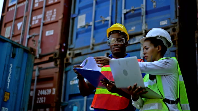 vídeos de stock e filmes b-roll de two african engineers with safety helmet holding laptop computer and clipboard checking shipping cargo containers in front of cargo container stacks in shipping container yard - docas