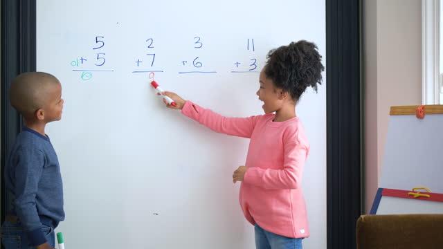 2人のアフリカ系アメリカ人の子供がホワイトボードで数学を行う - プラス記号点の映像素材/bロール