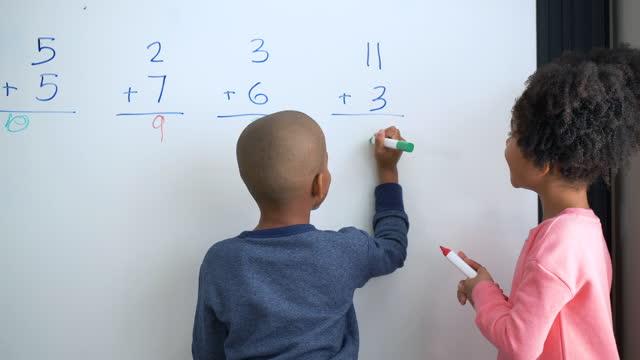 vídeos de stock, filmes e b-roll de duas crianças afro-americanas fazem matemática no quadro branco - 6 7 anos