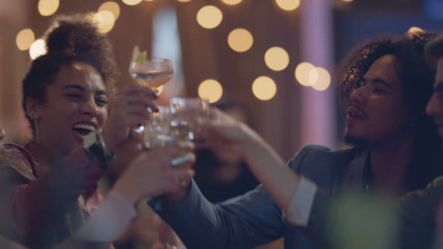 two african-american friends give a celebratory toast with friends at the bar - curly stock videos & royalty-free footage