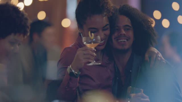two african-american friends hug while spending time with friends at the bar - long hair stock videos & royalty-free footage