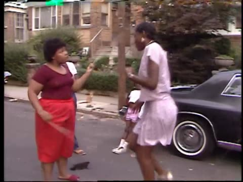 two africanamerican girls sing a tune while the other girl jumps in between jump ropes - minoranza video stock e b–roll
