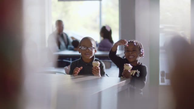 two african-american siblings play with their gummy worms while they eat ice cream - braided hair stock videos & royalty-free footage