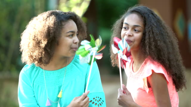 two african-american sisters playing with pinwheels - 12 13 years stock videos & royalty-free footage