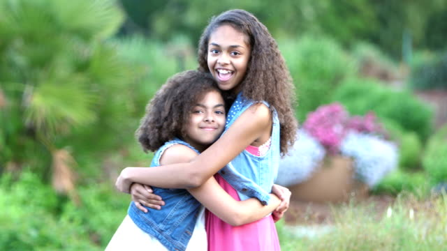 Two African-American sisters smiling in garden
