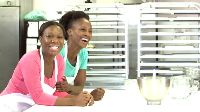 two african-american women in a bakery kitchen - forno video stock e b–roll