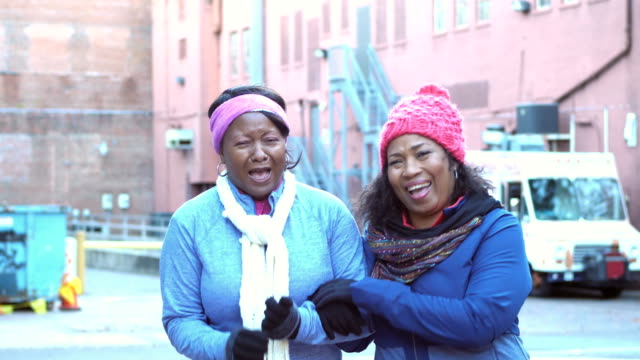 Two African-American women in warm clothing, laughing