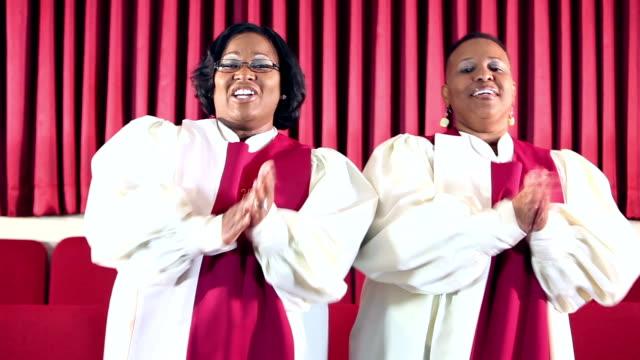 stockvideo's en b-roll-footage met twee afro-amerikaanse vrouwen in het kerkkoor zingen - gospelmuziek