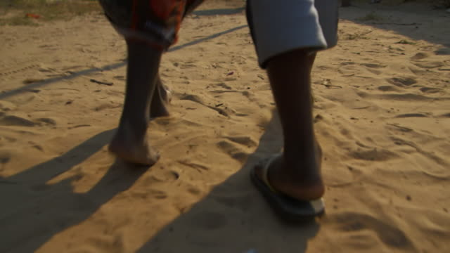 Two Africans walk down path low angle view
