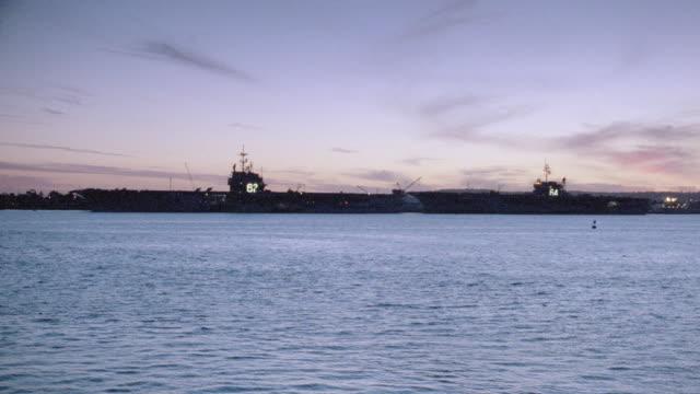 vidéos et rushes de two aircraft carriers float in a calm ocean. - être ancré