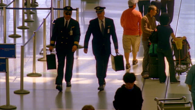 WS Two airline pilots walking through airport, talking / Los Angeles, California, USA