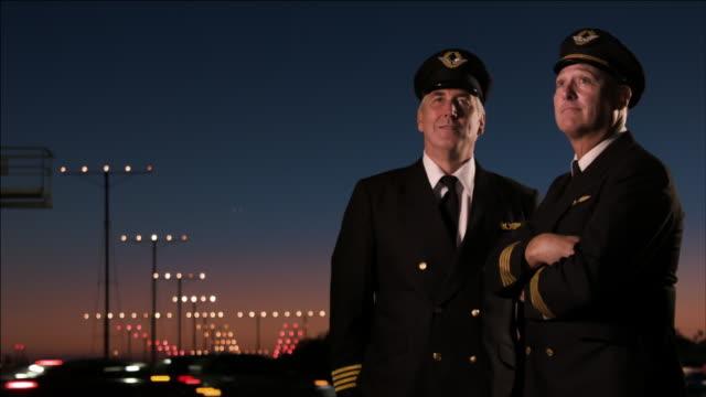 stockvideo's en b-roll-footage met m/s two airline pilots watch as airplane passes overhead on approach to landing, night: boeing-737 - armen over elkaar