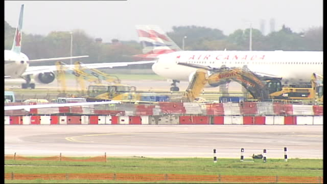 two airliners involved in collision at heathrow airport time lapse speeded up sequence aircraft along runway / bulldozers engaged in construction... - taxiway stock-videos und b-roll-filmmaterial