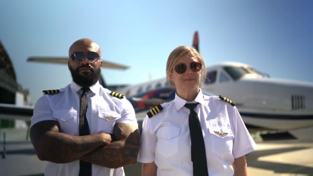 vídeos de stock, filmes e b-roll de dois pilotos do avião em um hangar e que olham a câmera - braços cruzados