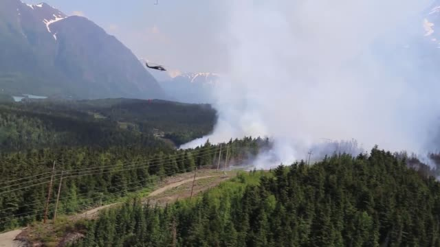 two alaska army national guard uh-60 black hawk helicopters from 1st battalion, 207th aviation regiment, flew a total of 200 bucket missions, dumping... - water fight stock videos & royalty-free footage