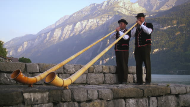 two alphorn players perform at lake's edge - wind instrument stock videos & royalty-free footage