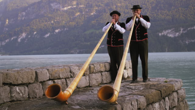 Two alphorn players perform next to lake