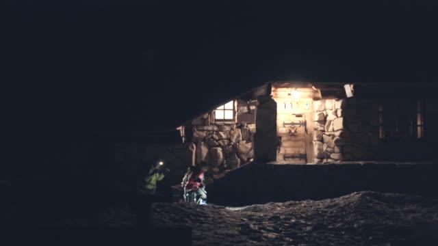 vídeos de stock, filmes e b-roll de dois alpinistas deixam o alojamento pequeno da montanha na obscuridade - 10 11 anos
