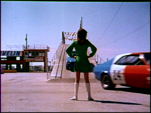 vidéos et rushes de ws two amc javelin race cars come over a bridge zo to xws of sexy woman wearing white gogo boots one javelin passes to her right the other to her... - 1960 1969