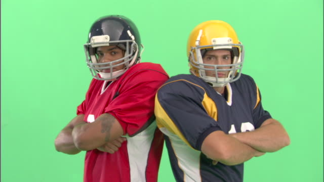 MS, Two American football players standing back to back in studio, portrait