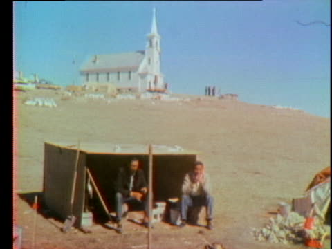 two american indians sit near a pile of firewood by a church and cemetery in wounded knee during a stand-off with the us government. - 1973 stock videos & royalty-free footage