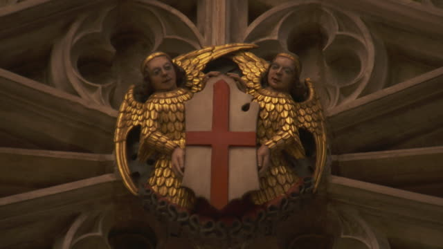 Two angels in relief hold the cross of St George in St George's Chapel Windsor Castle England FKAU104L Clip taken from programme rushes AEZQ152Y