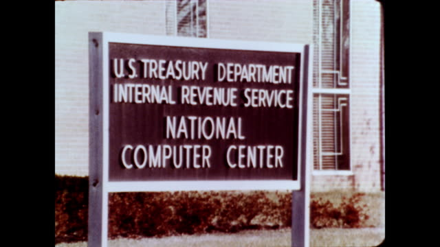 stockvideo's en b-roll-footage met / two animated tax return machines talking to each other / ext of irs building / cu sign that reads 'us treasury department internal revenue service... - informatiebord