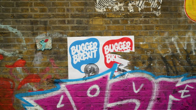 two anti-brexit posters are ripped and partially covered by graffiti on brick lane, london - brexit stock videos & royalty-free footage