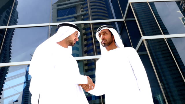 Two arab business people in handshake on the street -slowmotion