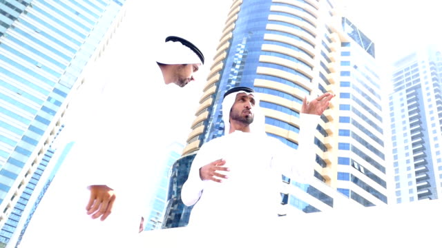 Two arab business people talking on the street -slowmotion